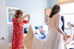 mother helping bride fix her dress